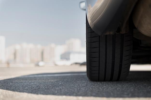 Rueda de un coche y ciudad borrosa en segundo plano. Foto gratis