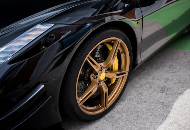 Rueda de coche sedán negro con decoración en color dorado y bronce. Foto gratis