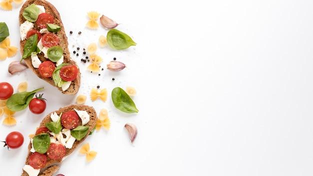 Sabrosa bruschetta; pasta farfalle cruda e ingredientes frescos aislados sobre fondo blanco Foto gratis