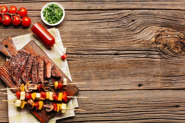 Sabrosa carne a la parrilla y brocheta con salsa de tomate. Foto gratis