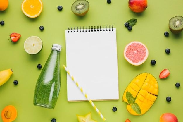 Sabrosa fruta fresca y jugo con cuaderno copyspace Foto gratis