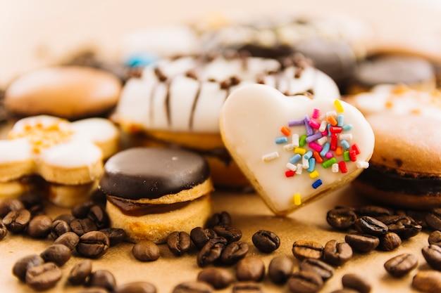 Sabrosa galleta en forma de corazón entre galletas y granos de café Foto gratis