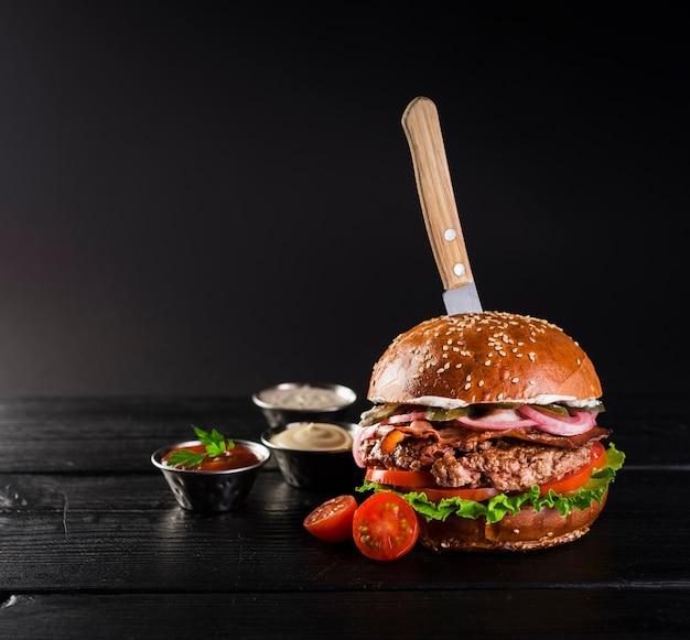 Sabrosa hamburguesa de ternera con cuchillo lista para ser servida Foto gratis