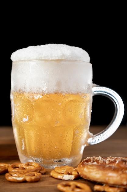 Sabrosa jarra de cerveza con espuma y pretzels Foto gratis