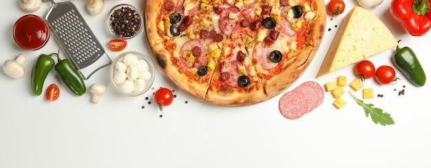 Sabrosa pizza e ingredientes en blanco Foto Premium
