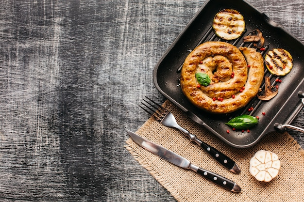 Sabrosa salchicha de caracol adorna con pimienta roja y albahaca Foto gratis