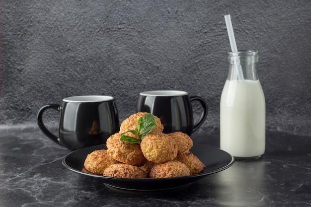 Sabrosas galletas de coco y bebidas en la mesa de mármol oscuro Foto Premium
