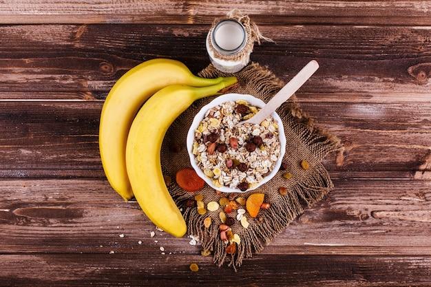Sabroso desayuno saludable por la mañana hecho de leche y gachas con nueces, manzanas y plátanos Foto gratis