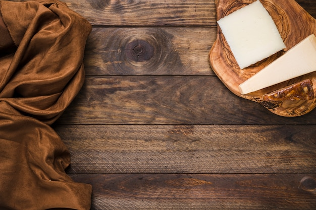 Sabroso queso en tabla de quesos de madera con tela de seda marrón sobre superficie de madera vieja Foto gratis