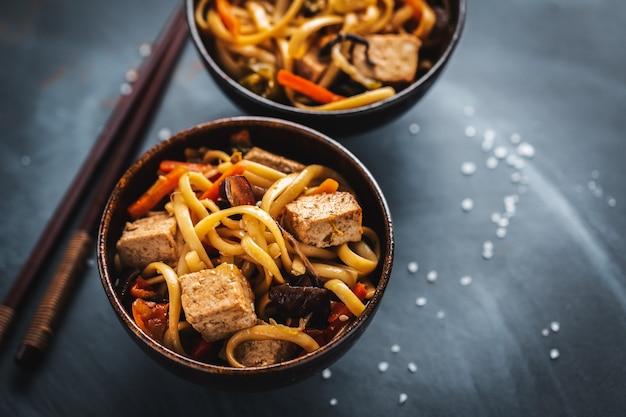 Sabrosos fideos asiáticos con queso tofu y verduras en tazones Foto gratis