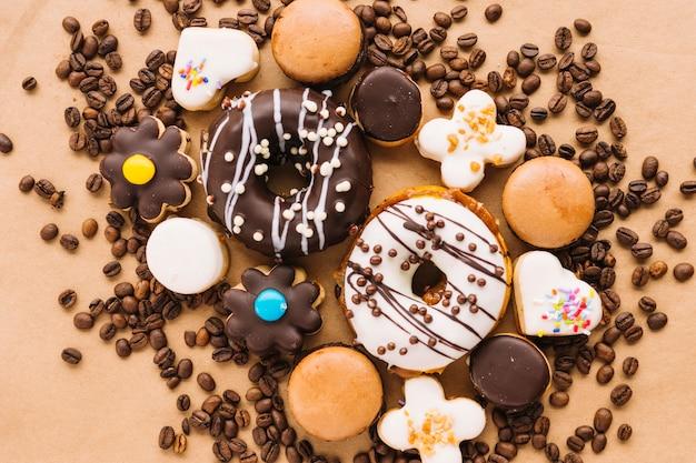 Sabrosos pasteles y galletas entre granos de café Foto gratis