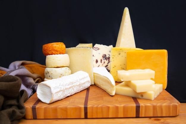 Sabrosos quesos diferentes en tabla de madera Foto gratis
