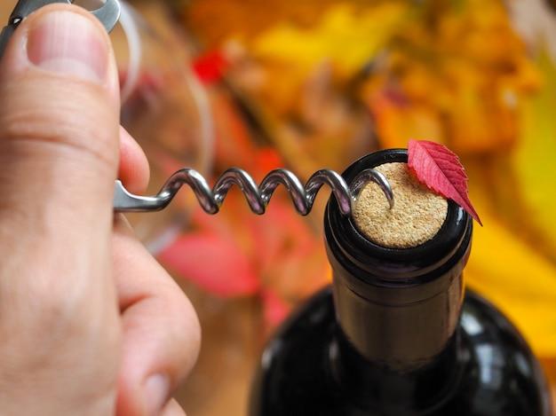 Sacacorchos y botella de vino tinto. abrir una botella de vino. de cerca. Foto Premium