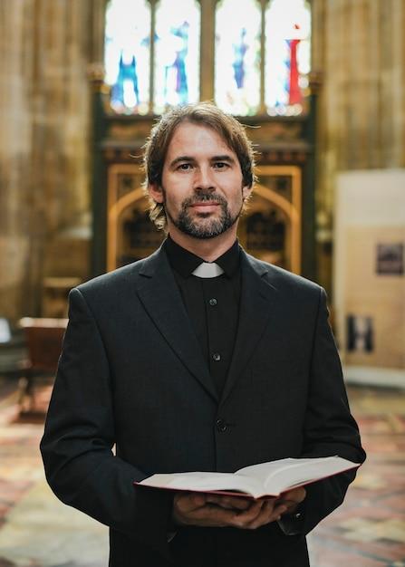 Sacerdote cristiano de pie junto al altar Foto Premium