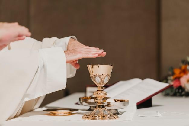 Sacerdote que sostiene la copa durante una ceremonia nupcial de la misa. concepto de religión Foto Premium