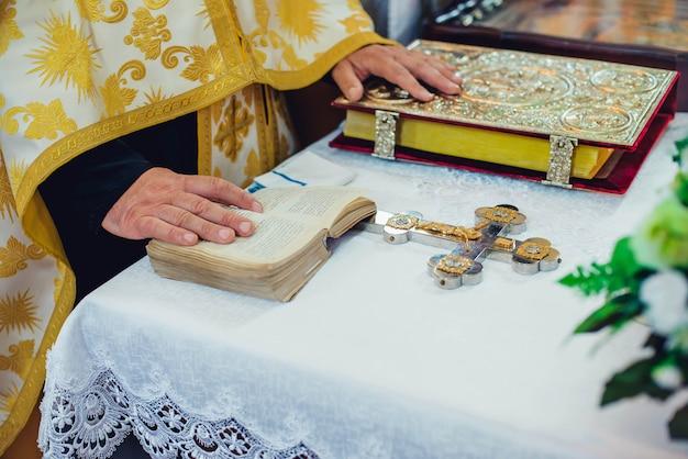 El sacerdote sostiene sus manos sobre los atributos ceremoniales de la boda en el altar en una iglesia Foto Premium