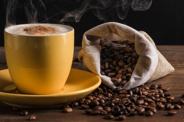 Saco de café y taza amarilla con plato. Foto gratis
