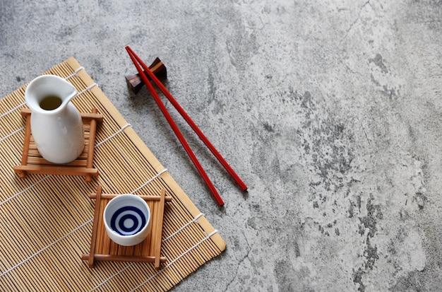 Sake japonés puesto estilo bebida oriental y palillos sobre la mesa Foto Premium