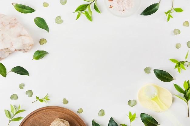 Sal de roca; cepillo; esponja y hojas sobre fondo blanco Foto gratis