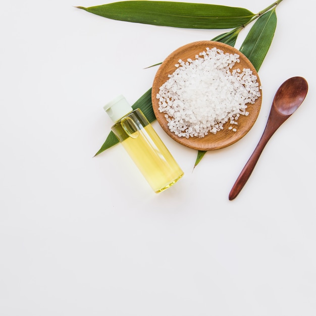 Sal de roca; hojas; cuchara y botella de spray de aceite esencial sobre fondo blanco Foto gratis