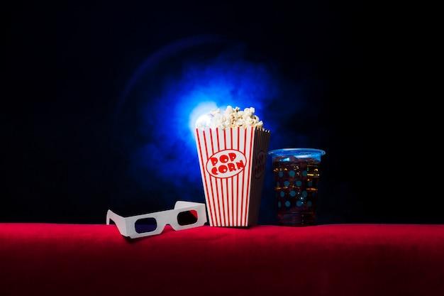 Sala de cine con paquete de palomitas y gafas 3d Foto gratis