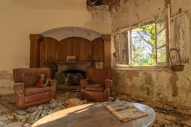 Sala de estar arruinada con chimenea en una casa abandonada Foto Premium