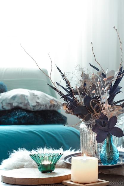 Sala de estar moderna, con flores artificiales en un jarrón y artículos de decoración del hogar en una mesa de luz de madera. Foto gratis