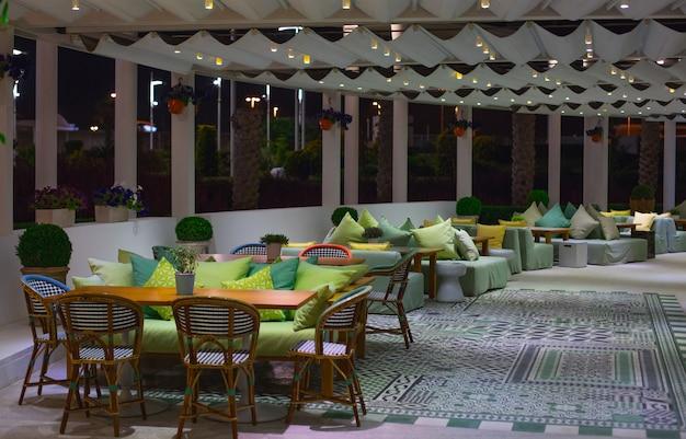 Una sala de restaurante con muebles de colores vivos y ventanas panorámicas. Foto gratis
