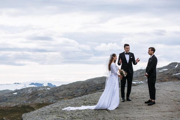 Salga de la ceremonia de boda en un fragmento de roca en noruega llamada lengua de troll Foto Premium