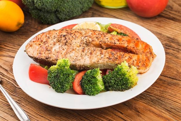 Salmón a la plancha con diversas verduras en un plato Foto gratis