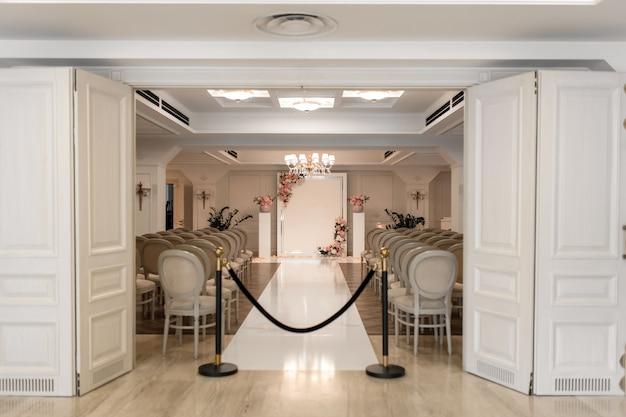 Salon de bodas. filas de sillas blancas festivas para invitados. arco de bodas para los novios. Foto Premium