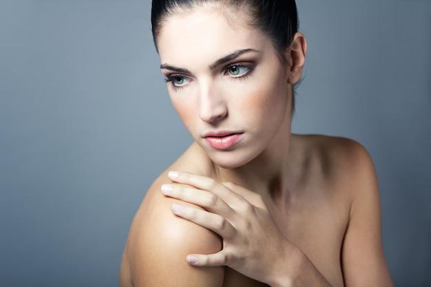 Salón de limpia mirando cámara hombros femenina Foto gratis