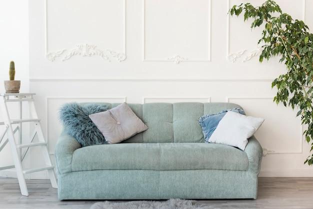 Salón luminoso con sofá grande gris en el centro. Foto gratis