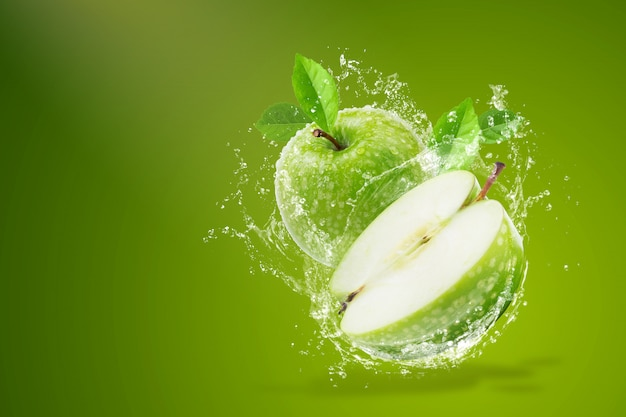 Salpicaduras de agua sobre manzana verde fresca sobre fondo verde Foto Premium