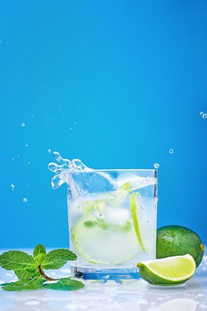 Salpicaduras de cóctel mojito con limón y menta fresca en vidrio sobre un fondo azul Foto Premium