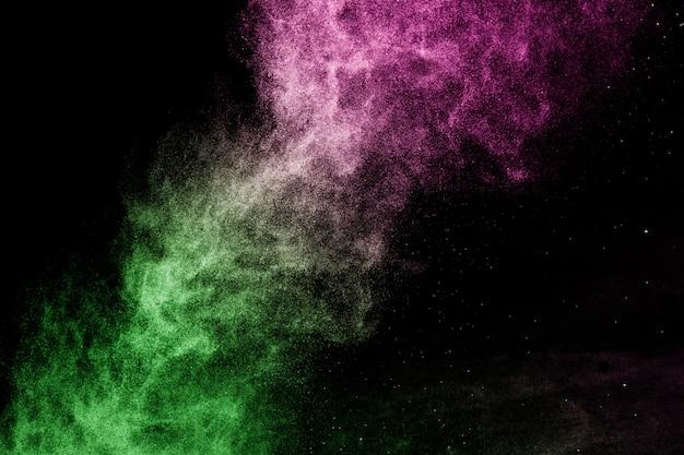 Salpicaduras de efecto de polvo verde y rosa para maquillador o diseño gráfico en fondo negro Foto Premium