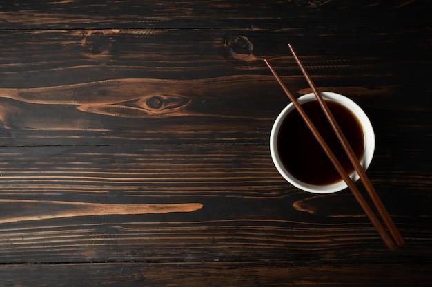 Salsa de soja y haba de soja en la tabla de madera. Foto gratis