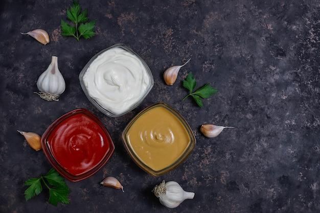 Salsa de tomate casera, salsa de mostaza y mayonesa e ingredientes en la oscuridad. vista superior Foto gratis