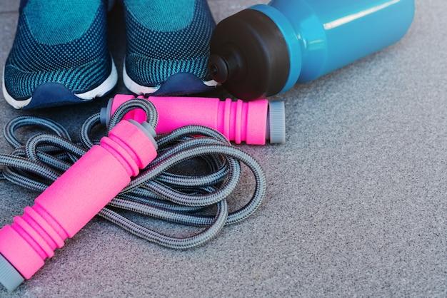 Saltar la cuerda, zapatillas y botella de bebida en el suelo Foto Premium