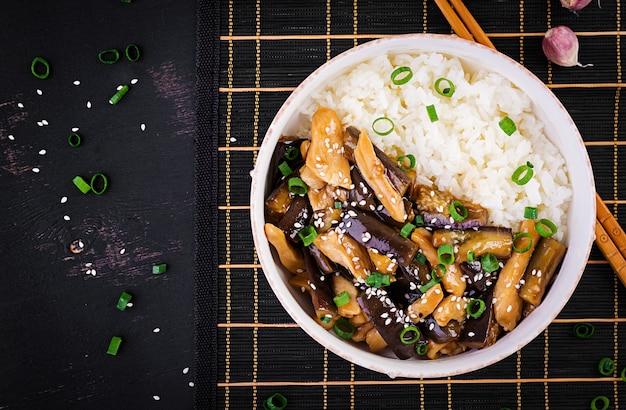 Salteado con pollo, berenjenas y arroz hervido Foto Premium