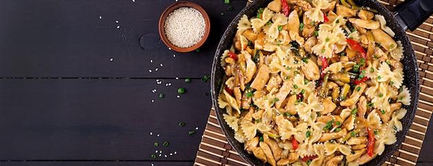 Salteado de pollo, pasta farfalle, calabacín, pimientos y cebolla verde Foto Premium