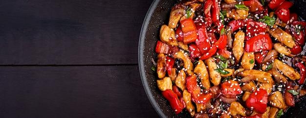Salteado de pollo, pimientos y cebolla verde. vista superior. cocina asiática Foto gratis