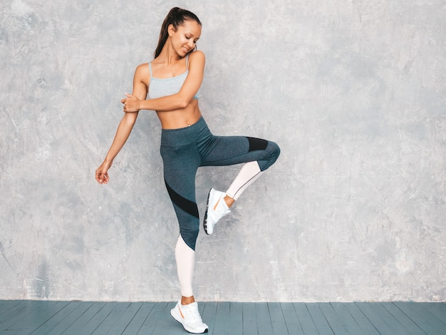 Salto femenino en estudio cerca de la pared gris Foto gratis