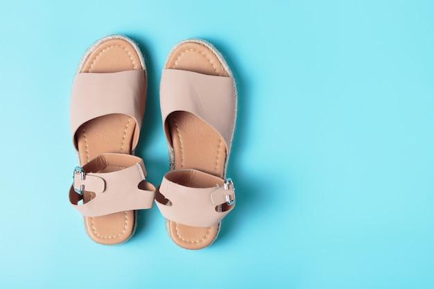 Sandalias de verano marrones, contra azul. primer plano, vista superior, una réplica del espacio Foto Premium