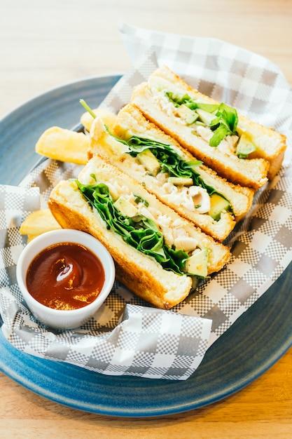 Sándwich con aguacate y carne de pollo con papas fritas. Foto gratis