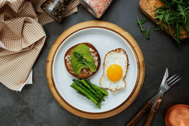 Sándwich de aguacate tostado y un huevo frito en un plato blanco con espárragos. comida saludable o desayuno. Foto Premium