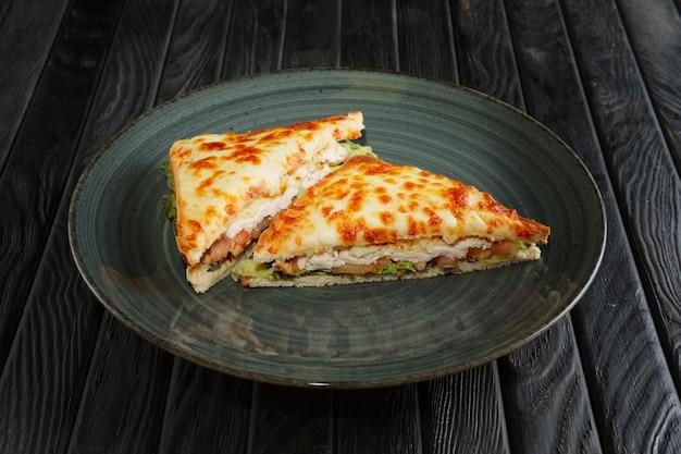 Sándwich club con filete de pollo, pepino en vinagre, ensalada y queso fundido Foto Premium