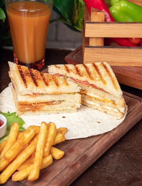 Sándwich club servido con papas fritas y refrescos, mayonesa, salsa de tomate Foto gratis