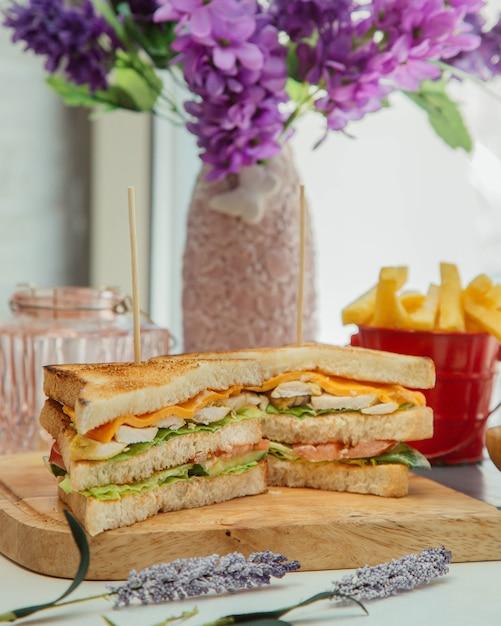 Sándwich club servido con papas fritas Foto gratis