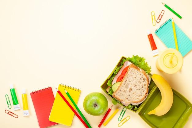 Sándwich fresco y manzana para un almuerzo saludable en la fiambrera plástica Foto Premium